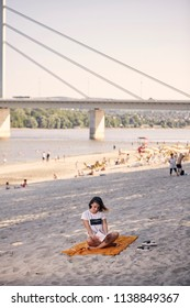 one young girl, relaxing reading a book outdoors, casual clothes, sunny day, laying on blanket, on sandy beach. unrecognizable people in background, river, coast, bridge.