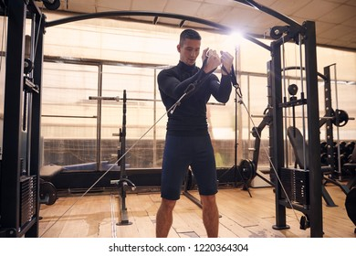 one young handsome man, 20-29 years old,  training in gym indoors, pulling cable chest exercisem on multi-station machine.