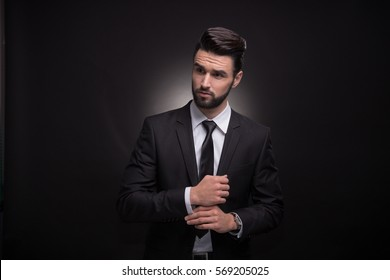 one young handsome man beard cufflinks hands, black background, elegant suit tie shirt pants