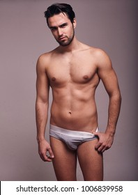 one young handsome man, looking at camera, shirtless, fashion model, gray background wearing briefs.