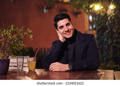 one young handsome man portrait, sitting in cafe garden at table, night sideways, smiling, looking to camera. upper body shot.