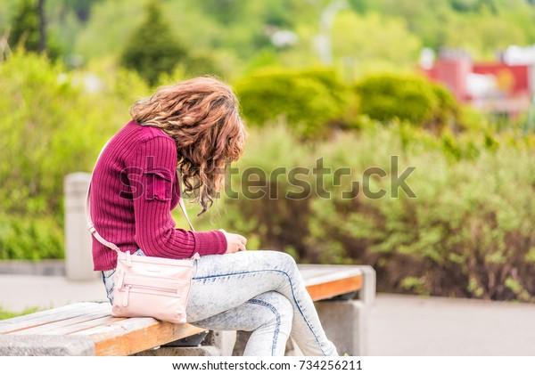 夏の間、ケベック州サグエナイの緑の繁華街公園の歩道に座る若い幸せな女性が、電話や本を見ている