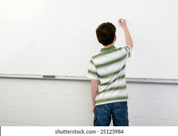 one young male student in a classroom writing on a whiteboard