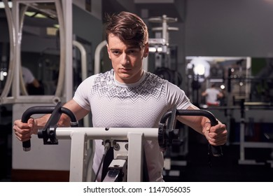 one young man 20 years old, fitness equipment exercise, indoors gym. upper body, medium shot. arm pull push