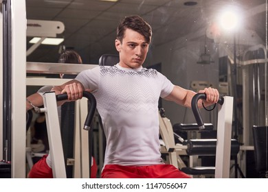 one young man 20 years old, fitness equipment exercise, indoors gym. upper body, medium shot. Seated Chest Press machine