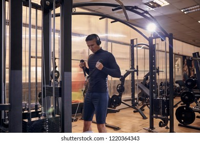 one young man, 20-29 years, training upper body on mult-station machine, indoors gym.