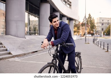 one young man, 20-29 years old, wearing suit, looking sideways,  smiling. posing on fancy city bicycle, leaning to front handlebar. upper body shot. modern architecture building behind.