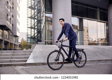 one young man, 20-29 years old, wearing suit, looking smiling. riding, pedaling standing, fancy  bicycle. full length body. modern architecture building behind.