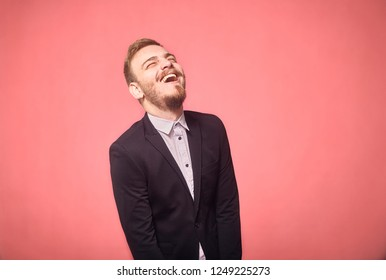 one young man, 20-29 years old, candid laughter, laughing. pink background, studio shot, photo shoot.