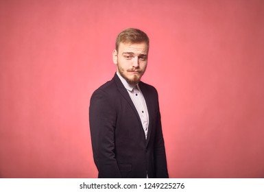 one young man, 20-29 years old, funny expression, acting funny with eyebrows, looking at camera. pink background, studio shot, photo shoot.