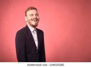 one young man, 20-29 years old, funny expression, candid laughter, eyes closed. pink background, studio shot, photo shoot.