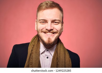 one young man, 20-29 years old, looking to camera, candid smiling happy. headshot, close-up of head/face, real person, not model. looking friendly. pink background, studio shot, photo shoot.