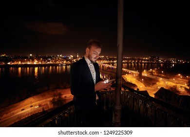one young man, 20-29 years old, formal clothes, wearing suit, using smart-phone. upper body shot. night time, dark, city scape behind in background (blurry, out of focus).