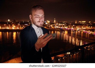 one young man, 20-29 years old, serious expression, formal clothes, wearing suit, looking at smart-phone. upper body shot. night time, dark, city scape behind in background (blurry, out of focus).