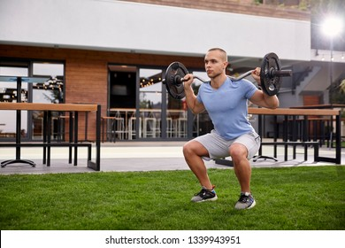 one young man, 20-29 years old, working out squat outside in his beautiful garden, side view.