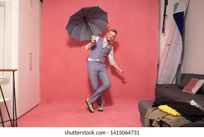 one young man, 20-29 years old, posing with an open umbrella inside a studio. shot in a studio, pink background.
