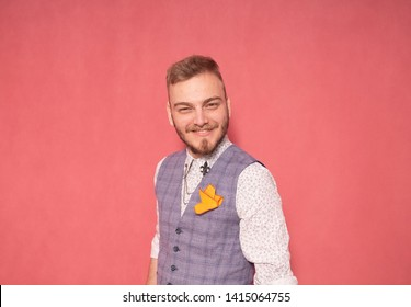 one young man, 20-29 years old, smiling at the camera, shot in a studio, on a pink background. wearing a suit.