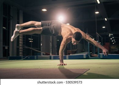 One young man, athlete, exercise one hand cartwheel. Dark large hall.