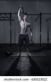 one young man bodybuilder, kettle bell, shouting screaming, dark gym indoors, black and white image.