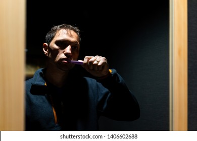One young man brushing teeth in bathroom with reflection in mirror and shadow night contrast lighting creepy sad