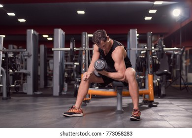 one young man, dark gym indoors fitness equipment, one hand dumbbell biceps exercise, sitting bench.