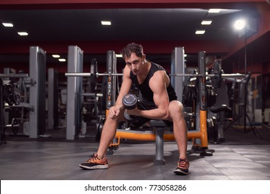 one young man, dark gym indoors fitness equipment, one hand dumbbell biceps exercise, sitting bench, looking at camera.