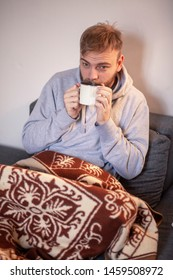 one young man, feeling sick, drinking tea while laying on a sofa