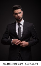one young man handsome elegant suit, black background, serious buttoning suit jacket