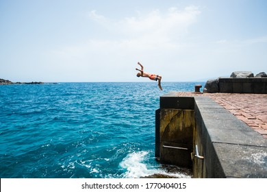 one young man jumping off a cliff doing a backflip to the water - alone fitness and healthy teenager having fun enjoying alone the summer and the sea in his holiday vacations