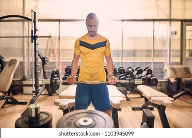 one young man, looking down, sport clothes, in old beaten up gym indoors, exercise equipment, exercising weight bar.