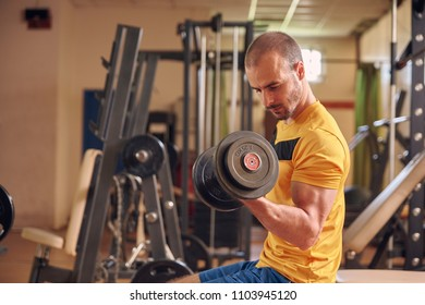 one young man, looking down sideways, profile view, sport clothes, in old beaten up gym indoors, exercise equipment, exercising biceps one arm dumbbell.