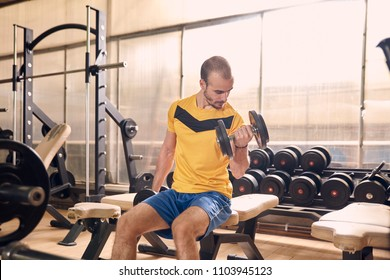 one young man, looking down sideways, sport clothes, in old beaten up gym indoors, exercise equipment, exercising biceps one arm dumbbell.