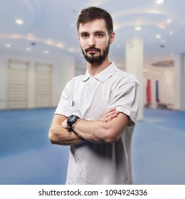 one young man, physiotherapist portrait. in blurred background exercising room.