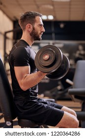 one young man, profile view, 20-29 years old, training dumbbell bicep curl, in gym, upper body shot.