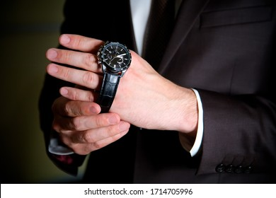 One young man puts a black watch on his wrist. A man in a black suit in a dark room.