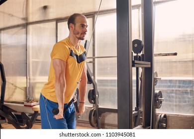 one young man, serious expression, wearing sport clothes, exercise on resistance bands, in old beaten up gym interior. western shot.