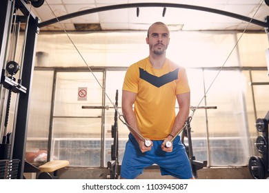 one young man, serious expression, wearing sport clothes, exercise on resistance bands, in old beaten up gym interior.western shot.