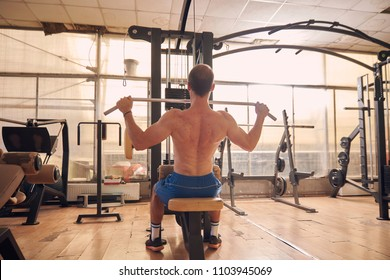 one young man, shirtless, back lat pulldown exercise, sitting multistationary machine  in old beaten up gym interior. full lenght shot, rear view.