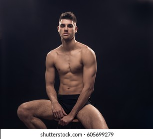 one young man, shirtless body sitting fit handsome, dark, black background