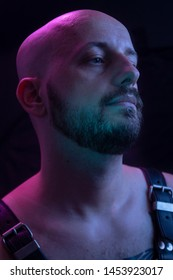 one young man, shirtless colorfully lit portrait, wearing a harness. upper body shot, looking sideways.