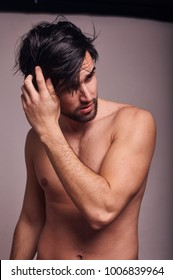one young man shirtless, messing with his hair, looking away from camera.