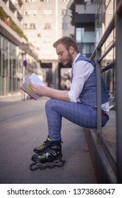one young man siting while wearing roller blades and holding a notebook. side view.