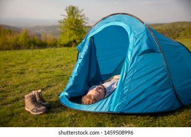 one young man, sleeping in small tent, in a grass field, in mountain.