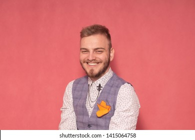 one young man, smiling to camera. wearing suit, upper body shot. not a model, real person (real people). Shot on pink background.
