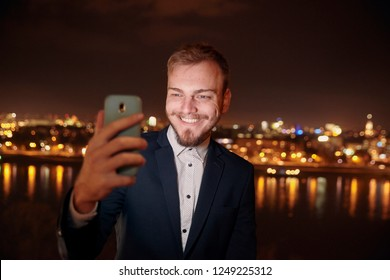 one young man smiling happy, 20-29 years old, formal clothes, wearing suit, looking at smart-phone, using camera, selfie, talking over phone. head face shot. night time, dark, city scape behind in blu