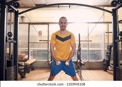 one young man smirking, wearing sport clothes, exercise on resistance bands, in old beaten up gym interior.western shot.