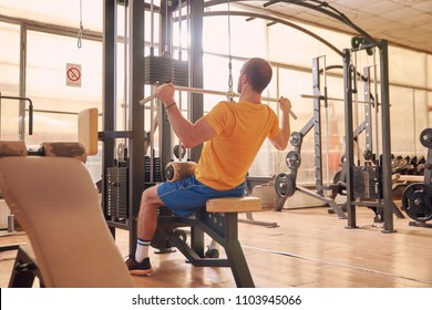 one young man, sport clothes, back lat pulldown exercise, sitting multistationary machine  in old beaten up gym interior. full lenght shot, rear view.