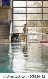 one young man swimmer posing near swimming pool, indoors.