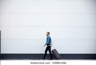 one young man - traveler or tourist, walking with a suitcase. building exterior white wall behind, minimalistic style.