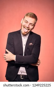 one young man, wearing suit and shirt, 20-29 years old, looking to camera, candid smiling happy, tongue out. real person, not model. pink background, studio shot, photo shoot.